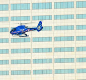 Helicopter and windows. Low flying helicopter flying past windowed modern building in city royalty free stock image
