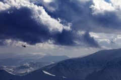 Helicopter in winter mountains and cloudy sky Royalty Free Stock Photos