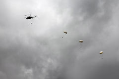 Helicopters dropped four parachutist, one after another Stock Photography