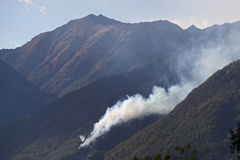 Helicopters dropping water on forest fire in the mountains Stock Images