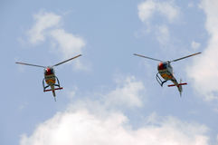 Helicopters flying in sync against sky Stock Photography