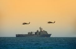 Helicopters hovering over ship Stock Photo