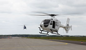 Helicopters landing. Two helicopters landing on a runway Stock Photos
