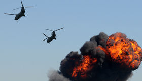 Helicopters over fire Stock Images