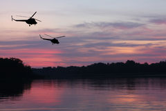 Helicopters in sunset sky Stock Photography