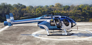 Helicoptor helipad Jammu Kashmir India. Landscape of a small metallic blue and white helicopter at a helipad waiting for passengers stock photos