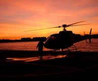 Helicóptero por el océano en la puesta del sol Foto de archivo
