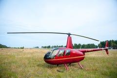 Helicóptero Robinson R44 en un prado cerca del airoport de Nida Fotografía de archivo libre de regalías