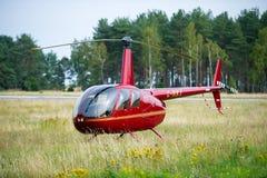 Helicóptero Robinson R44 en un prado cerca del airoport de Nida Foto de archivo