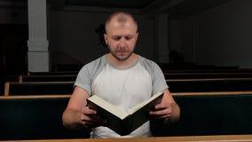 Helig bibel Man predikanten som ber till guden med hans h?nder som vilar p? en bibelultrarapidvideo Mannen l?ser en bok arkivfilmer