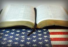 Helig bibel mot en amerikanska flaggan Royaltyfria Bilder