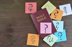 Helig bibel och färgrika anteckningsböcker med frågefläckar på brunt trä royaltyfri bild