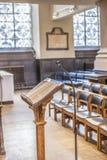 Helig bibel på en ställning i kyrkan framme av den prästEmpty kyrkan med fokusen på bibeln royaltyfri fotografi