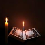 Helig bok av islam med stearinljusljus Arkivfoton