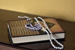 Helig bok för islamisk bön med pärlrosmarin som isoleras på reflekterande bakgrund royaltyfri fotografi