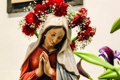 Helig Mary staty i kristen kyrka med nya blommor arkivbilder
