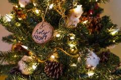 Helig natt för nolla och andra prydnader på ett julträd arkivfoto