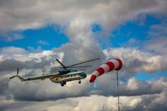 Helikopter die in bewolkte hemel en windcone vliegen stock foto's