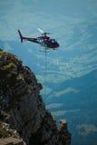 Helikopter die bouwgoederen vervoeren aan bouwwerf in Zwitserse alpes Stock Foto