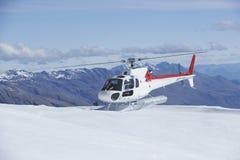Helikopter die op Sneeuwbergbovenkant landen Stock Foto