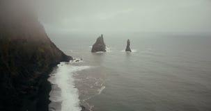 Helikopter die over de mooie zwarte vulkanische strand en sleeplijntenenklippen vliegen in IJsland Landschap van overzees, mist e stock footage
