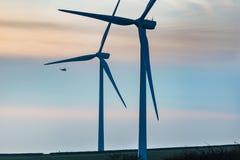 Helikopter die voorbij windturbines vliegen Stock Foto's