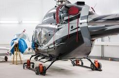 Helikopter en een klein sportenvliegtuig in de hangaar Stock Afbeeldingen
