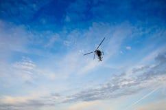 Helikopter i himlen med moln Fotografering för Bildbyråer