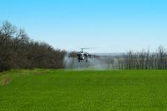 Helikopter met nevel boven landbouwgebied op het landbouwbedrijf in de lente stock afbeelding