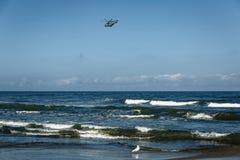 Helikopter nad morzem przeciw bezchmurnemu niebu zdjęcia stock