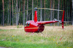 Helikopter Robinson R44 in een weide dichtbij Nida airoport Stock Foto