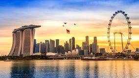 Helikopter Singapore för nationell dag som hänger den Singapore flaggan som flyger över staden royaltyfria bilder