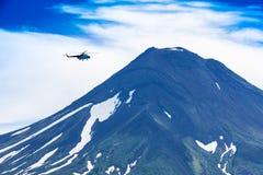 Helikopter som flyger över den Ilyinsky vulkan och Kurile sjön arkivbilder