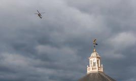 Helikopter som flyger över ett fåfängt för väder på ett molnigt dystert mörker Da royaltyfri foto