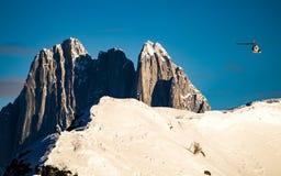 Helikopter som flyger över snöig och steniga berg Arkivbilder