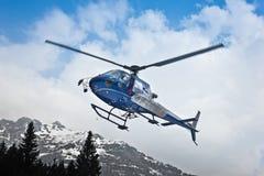 Helikopter som lämnar i berg Arkivbild