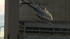 Helikopterelevatorer av och flugor mellan byggnader arkivfilmer