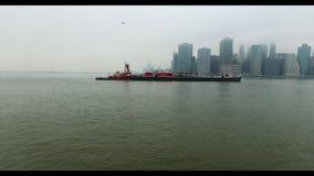 Helikopterflyg över Hudson River Avlägsen sikt av Manhattan och färjan som svävar vid vattnet lager videofilmer