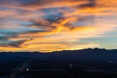 Helikopterflyg på solnedgången över stad royaltyfria foton