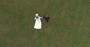 Helikoptermening van huwelijk Bruidegom en bruid die hoewel thw groot die park lopen door bos wordt omringd stock footage