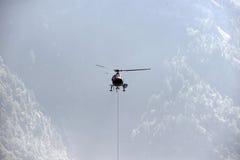 Helikoptern bär last i fjällängarna Royaltyfri Bild
