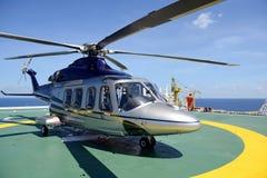 Helikoptern parkerar på oljeplattformplattformen för att välja upp arbetaren med b Royaltyfri Fotografi