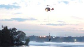 Helikoptern samlar vatten i floden för att släcka en brand Räddningstjänsten och brandmännen släcker branden arkivfilmer