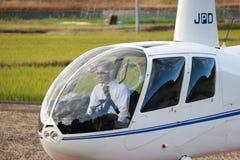 Helikopterpilot i lopphelikoptern JA002R - ROBINSON R44 som ÄR KORPSVART från Robinson Helicopter Company Arkivfoto