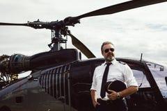 Helikopterpilot i solglasögon med helikoptern royaltyfri bild