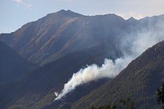 Helikopters die water op bosbrand in de bergen laten vallen Stock Afbeeldingen