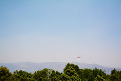 Helikoptervlieg over berg en boom in een duidelijke hemel Royalty-vrije Stock Foto's