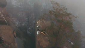 Helikoptervlieg over de rotsen waar de mens in geel jasje over de mist beklimt Bloem in de sneeuw stock videobeelden