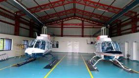 Helikoptrar i hangar Arkivbild