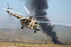 Helikoptrar som monterar en jordattack med explosioner och rök Arkivbild